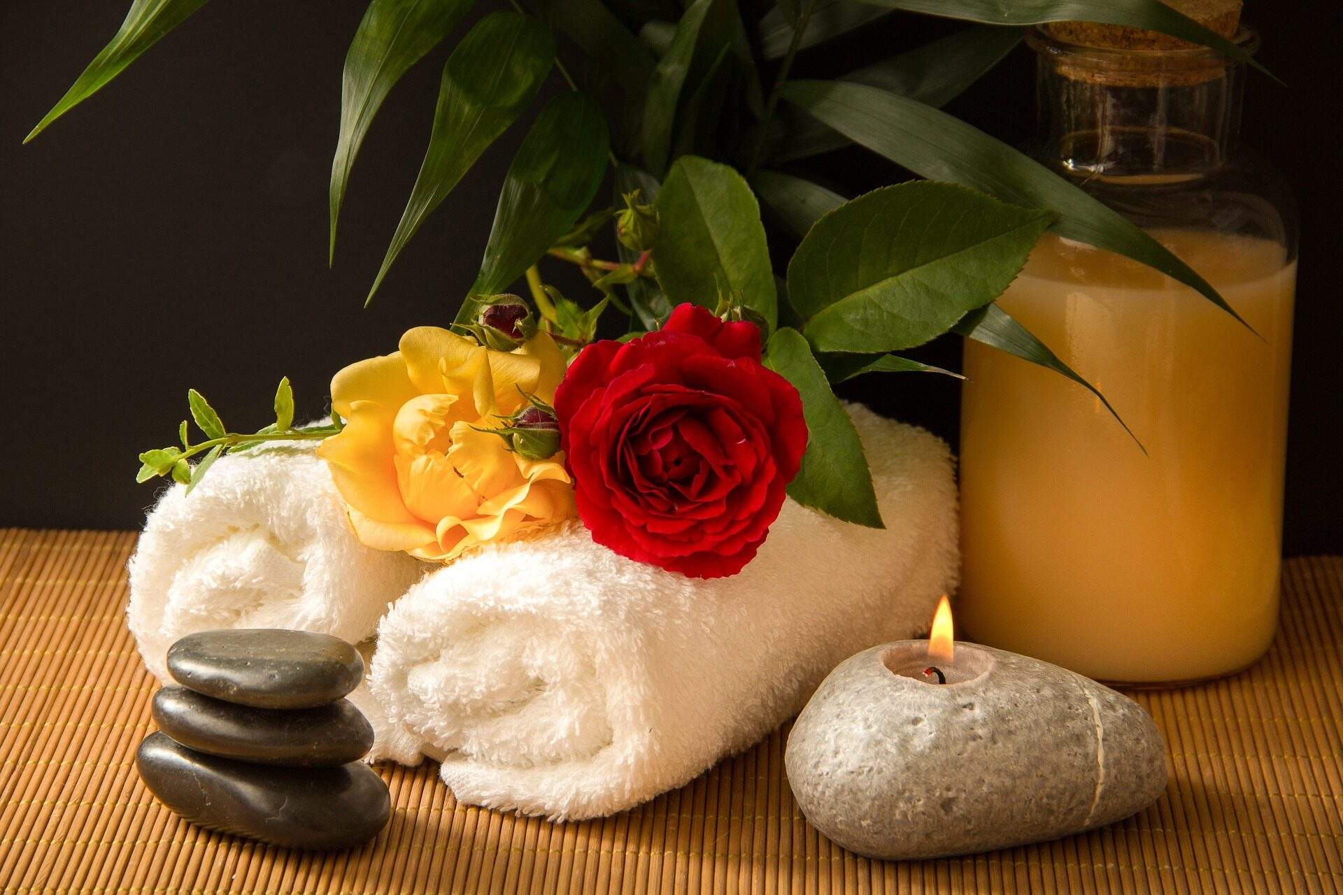 spa candle with towels and stones