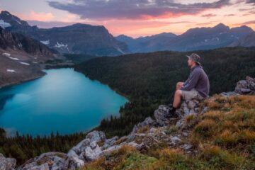 hiker sitting on rock overlooking lake at sunset