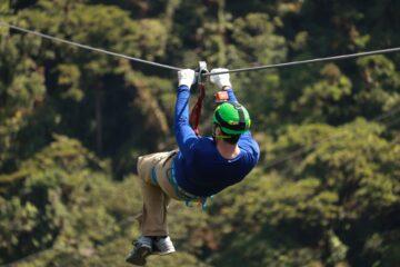 man in blue shirt with green helmet on a zipline