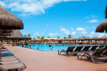 swimming pool with tiki huts around it